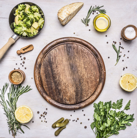 close up view: raw broccoli in a small frying pan, parsley, oil, salt, lemon, pickles laid out around a cutting board place for text,frame on wooden rustic background top view close up Stock Photo