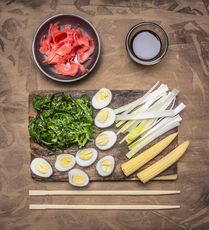 japanese quail: concept cooking Chinese food, boiled quail eggs with seaweed Chuka, and corn on wooden rustic background top view Stock Photo