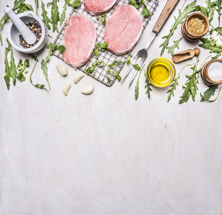 bbq background: Ingredients for cooking pork with herbs and pepper border, place for text on wooden rustic background top view