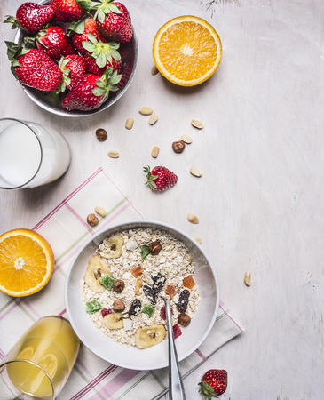appetizing breakfast with fresh strawberries, oatmeal, orange juice border, place for text on wooden rustic background top view close up