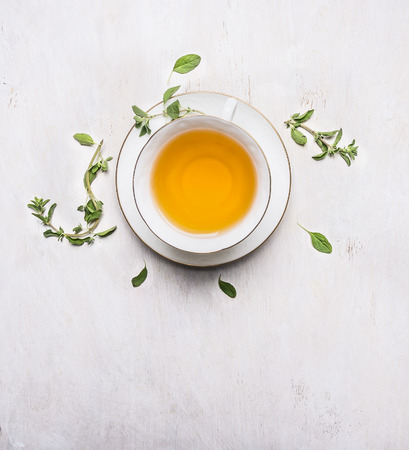 tea with thyme in a white cup on a white saucer place for text on wooden rustic background top view