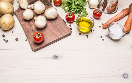 cooking vegetarian food, fresh mushrooms, carrots and parsley oil potatoes border, place for text on wooden rustic background top view