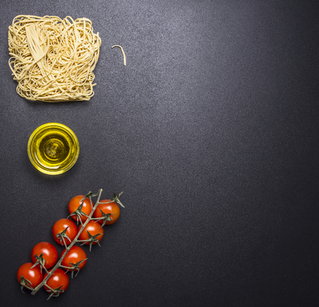 egg noodles: egg noodles with cherry tomatoes and oil border ,place for text on wooden rustic background top view Stock Photo