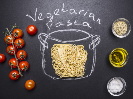 seasonings: vegetarian cooking pasta, painted pot, cherry tomatoes, Oil and seasonings on wooden rustic background top view Stock Photo