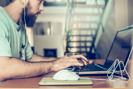 two floors: man with a beard is working at the computer, on the background of two floors of apartments Stock Photo