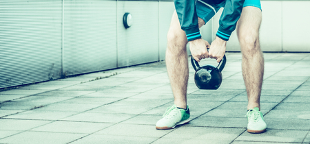 hairy: Sporting Life, spring training on the street, young man lifts a weight Stock Photo