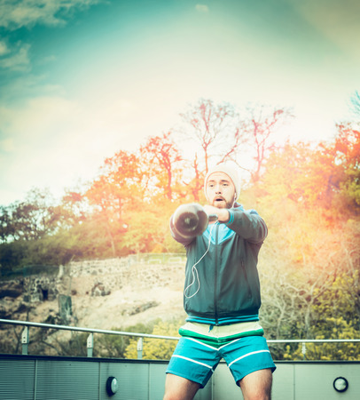 jungle gyms: young man training with weights on the terrace of the house of the forest and sunset sky background Stock Photo