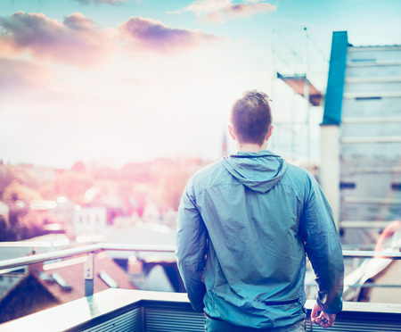 admires: young man in gray jacket with short hair, standing on the balcony of the house and admires the sunset blurred cityscape Stock Photo
