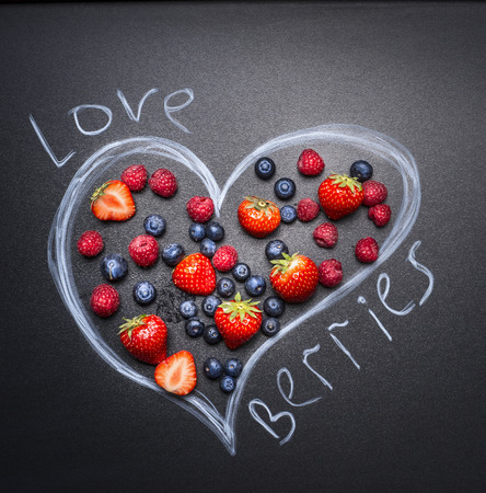 laid: fresh berries, blueberries, strawberries and raspberries, are laid out in the drawn heart on the chalkboard top view Stock Photo