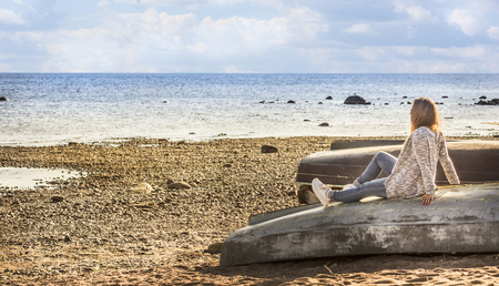 upturned: girl sitting on the beach on the upturned boat and looking at the water, the sea and beach landscape with blue cloudy sky, holiday, vacation