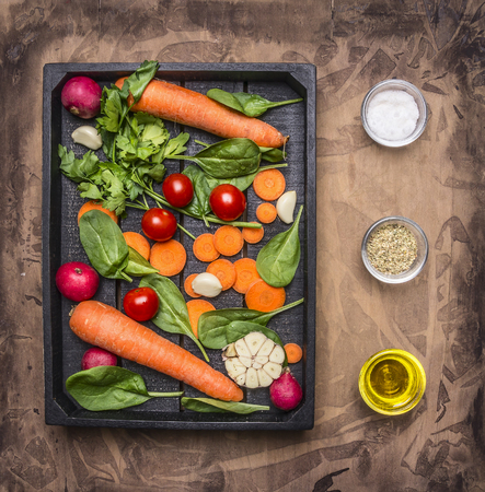 spread around: Delicious assortment of farm fresh vegetables  sliced carrots, fresh spinach leaves, seasonings and butter, cherry tomatoes laid out in a wooden box, spread around spices and herbs Stock Photo