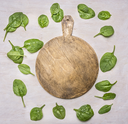 laid: fresh spinach leaves, laid out around a cutting board place for text,frame Stock Photo