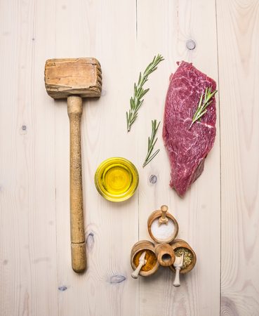 beating: concept cooking raw beef steak, rosemary, wooden hammer for beating the meat, oil, herbs and spices on wooden rustic background top view close up