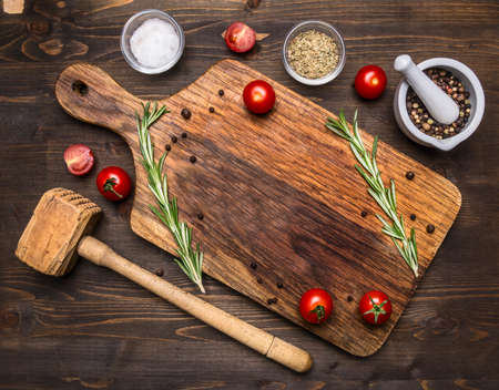 thai herb: old cutting board with spices and herbs for cooking meat with cherry tomatoes and a hammer for meat place for text, frame