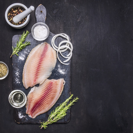 preparation of raw tilapia fillets with salt, oil and herbs, whole pepper in a mortar, laid out on a chopping board on a dark rustic background Border with space for text top view