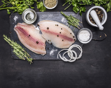 raw fillet of tilapia with spices and herbs, lemon and pepper on a cutting board on a white background rustic village top view