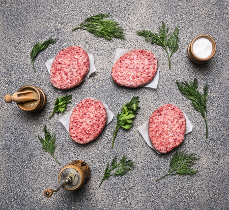 encurtidos: casera chuleta crudo, en un mostrador de la cocina de granito, el concepto de cocinar hamburguesas, junto forrado especias y hierbas vista desde arriba Foto de archivo