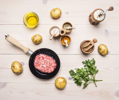 roasting pan: raw homemade burgers in a pan with spices, herbs, potatoes and butter on rustic white wooden table