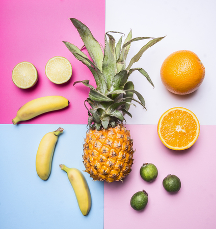 concept of summer fruit set against a bright background mini pineapple, mango, mini bananas, carambola, lime, quince, top view