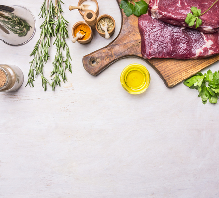 concept of cooking meat, raw ribeye steak on a cutting board with rosemary, spices, oil and vegetables, with a meat cleaver vintage, Border, place for text on a rustic wooden background Banco de Imagens