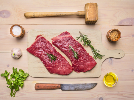 appetizing pork raw steak on a white cutting board with rosemary, herbs and spices, with a knife and a hammer for meat