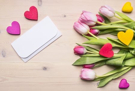 Fresh bouquet of tulips as a gift for a mothers day, envelope, decorative hearts, place for text, on a rustic wooden background background
