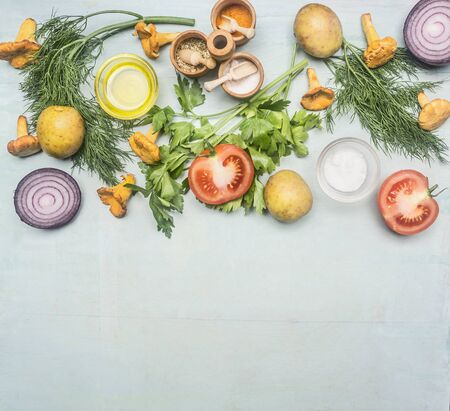 Ingredients for cooking chanterelles with vegetables and herbs, laid out on a blue rustic background, space for text border