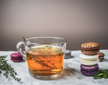 Healthy hot herbal tea with berries, thyme and mint, appetizing, multicolored macaroons, piled on a white rustic background, space for text