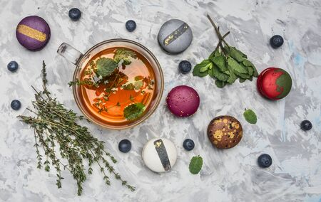 healthful hot herbal tea with berries, thyme and mint, appetizing, multicolored macaroons on a white rustic background, top view Stock Photo