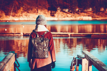 Girl traveler in autumn clothes, long hair and a backpack behind her shoulders, stands on the lakeside by the lake, against the background of yellow trees and water Stock Photo