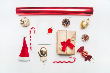 Christmas or New Year composition, Santa Claus hat, lollipops, gift in a box with a bow, red packing paper lined up on a white background, top view, flat lay