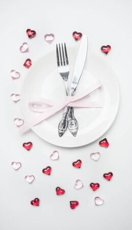 composition for Valentines day knife and fork tied with ribbon on a plate with decorative hearts