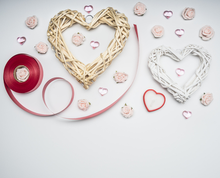 composition for Valentines day, decorative hearts and flowers, with red ribbon, on white background, top view, space for text