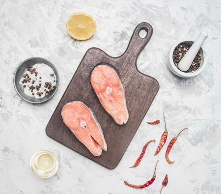 two delicious raw salmon steaks with lemon, seasoning and pepper on a white background, top view Reklamní fotografie