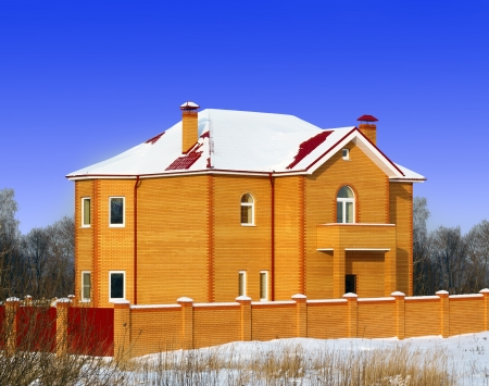 residental: The new brick house from the yellow bricks with the red metal roof and two chimneys at the blue sky