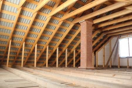 trussing: Struttura del tetto in legno coperto da lamiera profilata e camino in mattoni vista interna Archivio Fotografico