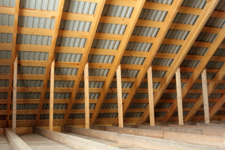 Wooden roof frame covered by profiled metal sheet inside view photo