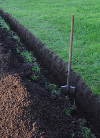 open trench: Trench in the ground at the lawn and the spade