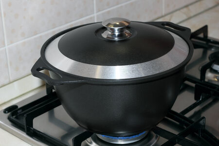 Black metal pot covered with a lid on the gas stove  photo