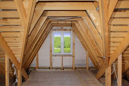 attic: Attic under construction (wooden roof frame and plastic window) Stock Photo