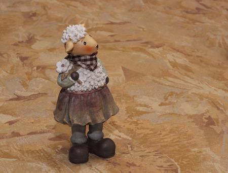 statuette: Ceramic sheep statuette on the textile background photo