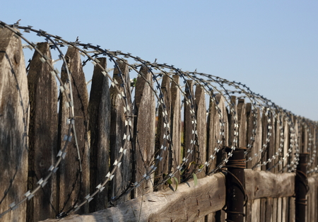 barbed wire fence: Old wooden fence with barbed wire perspective photo