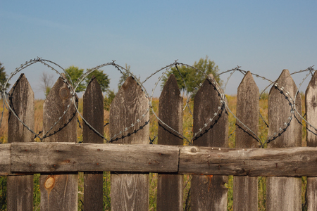 barbed wire fence: Old wooden fence with barbed wire photo