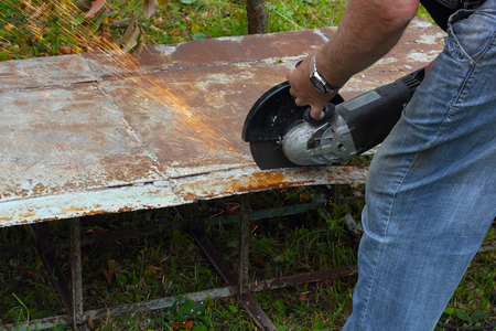 Worker cuts metal sheet by angle grinder photo Stock Photo