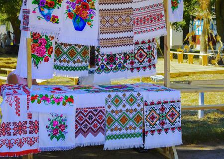 punto de cruz: Venta de tejidos bordados a mano en la feria del pueblo