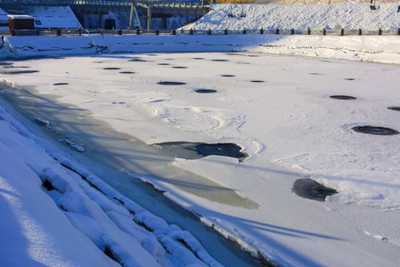 Warm water on the ice of a frozen lake covered with ice in winter