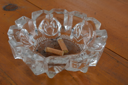 Dirty ashtray with cigarette butts on the table