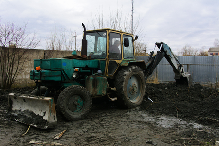 dirty car: An old Soviet tractor digs and loads waste stone processing near the shop