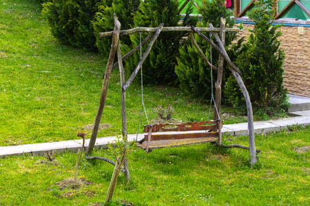 empty wooden brown swing on grass in summer Stock Photo