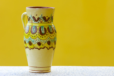 Earthenware figurines, decorative figurines, vase, isolated on a yellow background